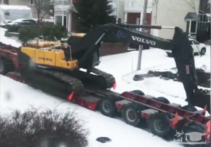 (فیلم) تلاش جالب بیل مکانیکی برای نجات تریلی از جاده برفی