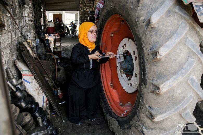 یک زن در حال تعمیر تراکتور
