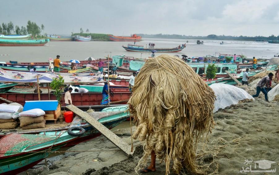 یک کارگر بنگلادشی در حال حمل کنف به داخل قایق
