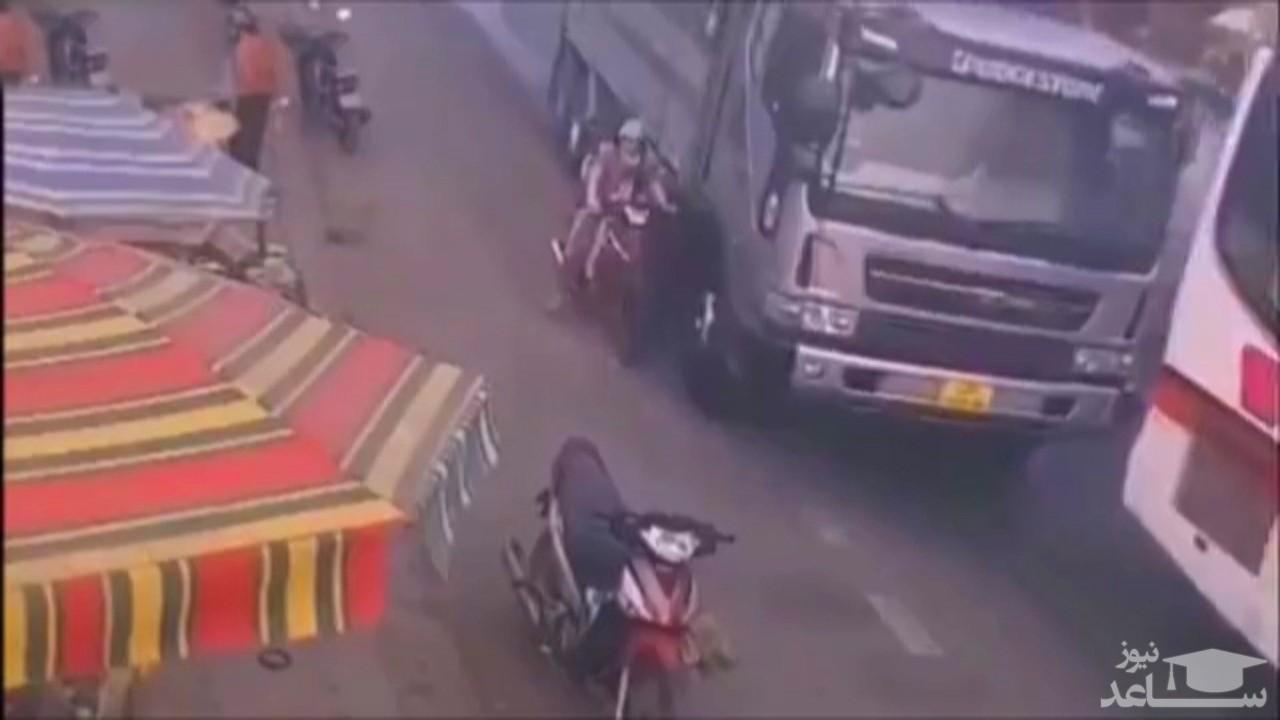 (فیلم) زنده ماندن معجزه آسای زن موتورسوار و فرزندش پس از تصادف با کامیون