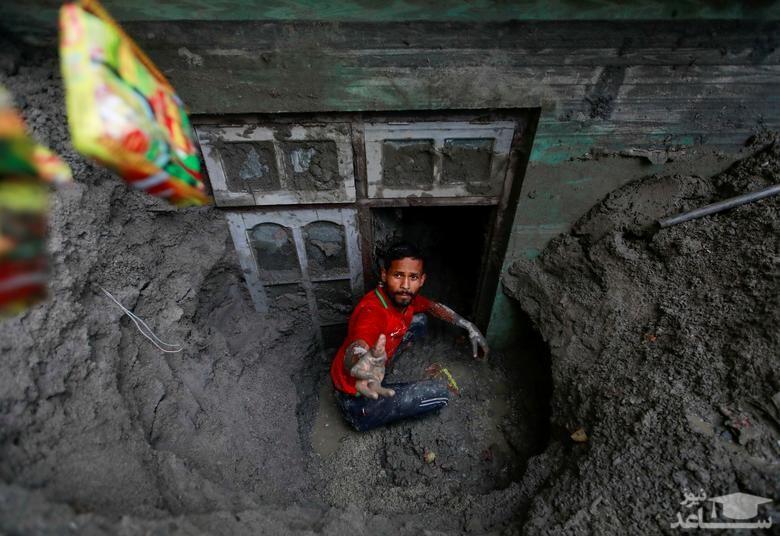 دفن خانه ها در گل و لای سیلاب در نپال